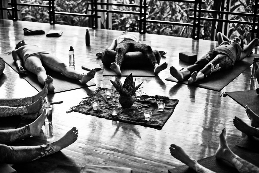 black and white of a group of women laying on their backs meditating at a retreat