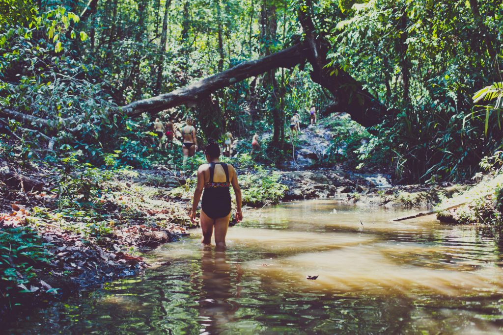 image of a woman walking through a river in the costa rica jungle in a bathing suit