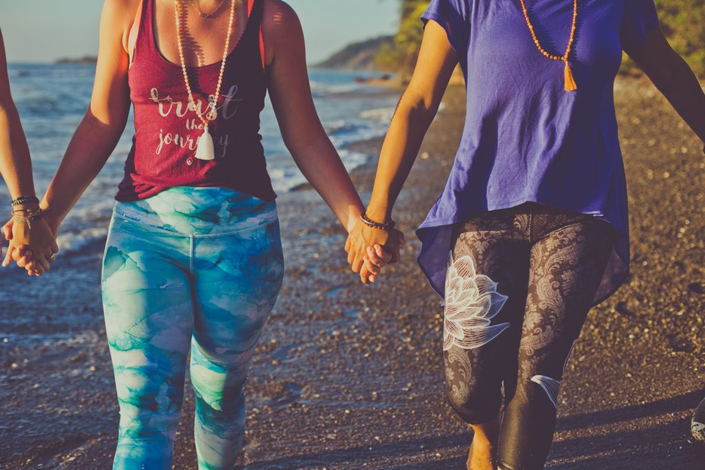 image of two women holding hands and walking on the beach
