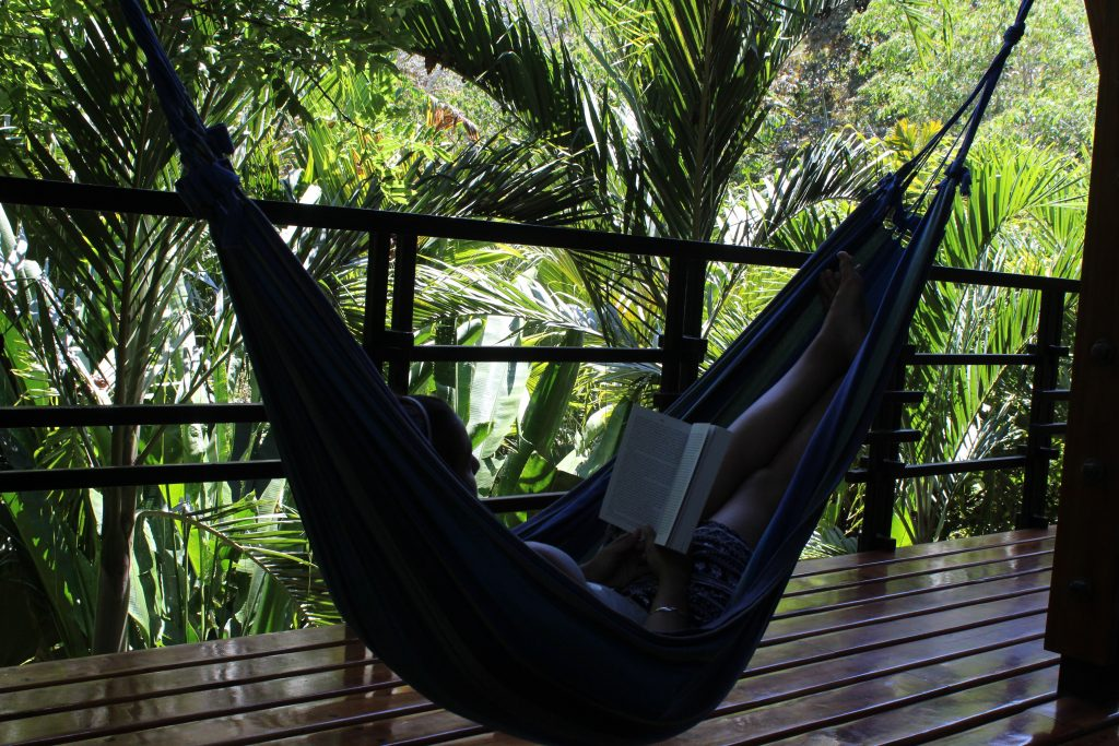 image of woman laying in a hammock in the jungle reading a book