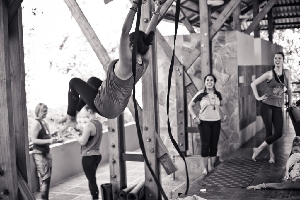 black and white image of a woman swinging on rings at a retreat