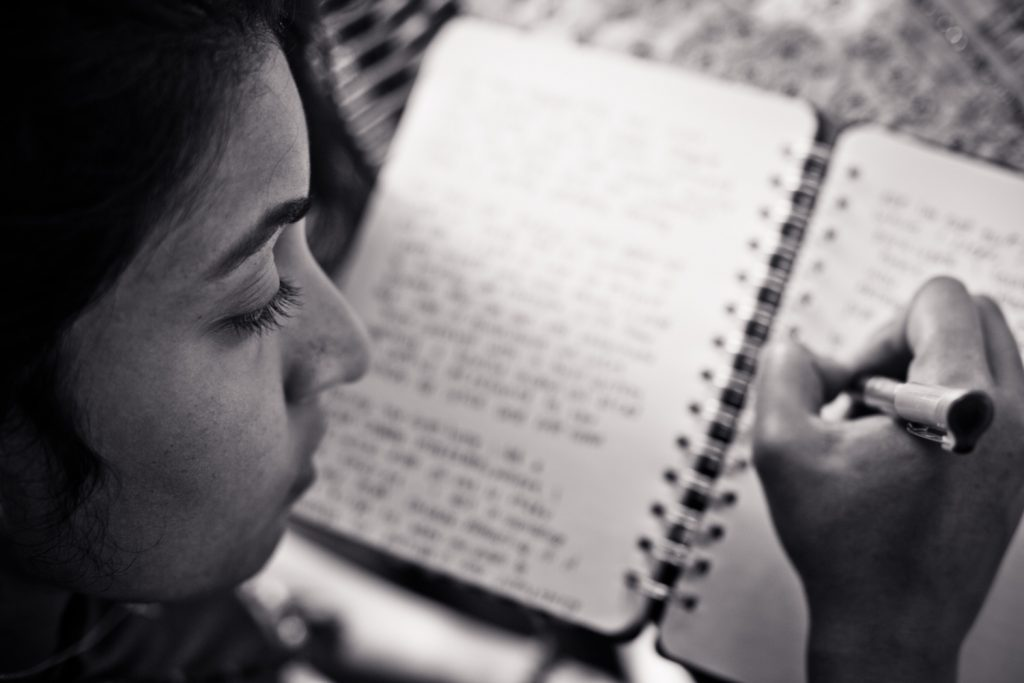 black and white image of a woman journalling