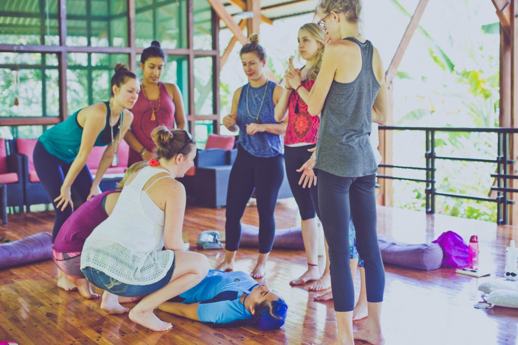 image of a group of women standing over another woman at a retreat